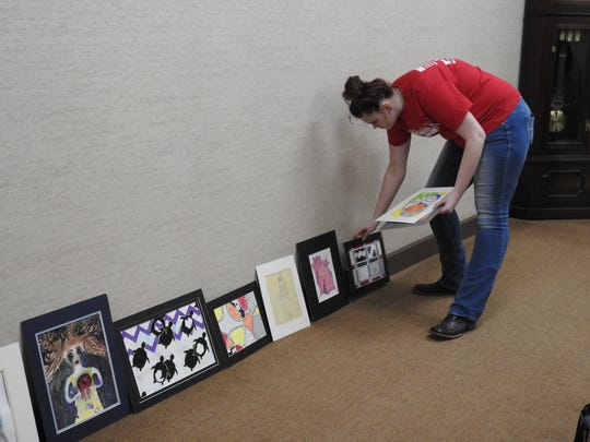 Ridgewood Sophomore Alexandria Thompson sets out artwork to be hung as part of the Teen-Age Talent exhibit opening at the Johnson-Humrickhouse Museum.