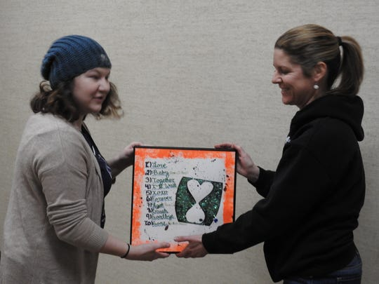 Amanda Matchett and Carissa Dickerson prepare to hang a piece for the Teen-Age Talent exhibit at the Johnson-Humrickhouse Museum.