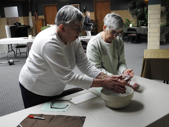 Ruth Gilmore and Nancy Jackson wash their hands after