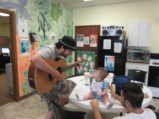 Sean Swart, left, playing guitar for his nephew Gavin.