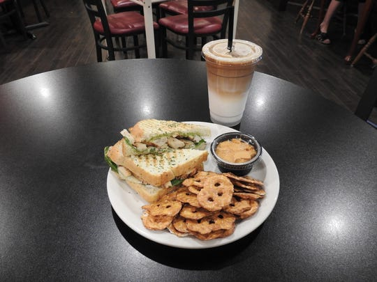 The chicken pesto panini is one of the most popular items on the menu and is featured with pretzel chips, hummus and coconut mint latte.