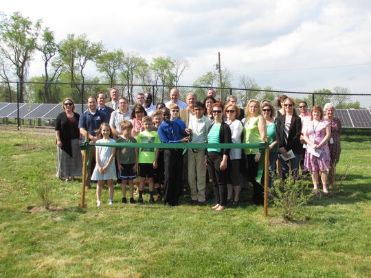 Sixth grade students Rooney Rasare and Christopher Serrao (front center) stand get ready to cut the green ribbon.