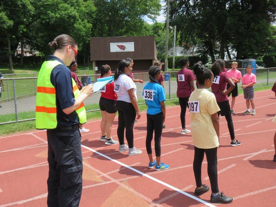 Rotary volunteer Brian Townley checks in runners for the 13-year-old girls 100 meter event.
