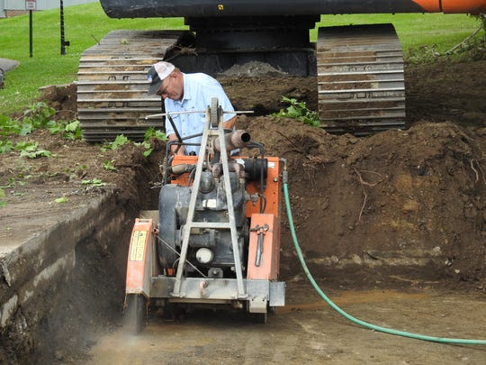 Don Wells of William Albert Excavating works Tuesday to clear concrete from a hole on North Whitewoman Street. A void from an old spillway was discovered during a recent waterline project.