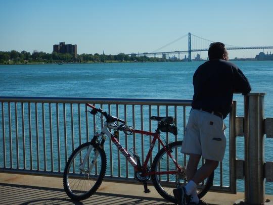 A cyclist pauses along the Detroit International RiverWalk.
