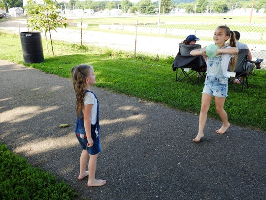 Chloe Davis, 9, prepares to throw a ball to her sister, Susan Hayes, 6, before the fireworks started Tuesday at the Coshocton County Fairgrounds.
