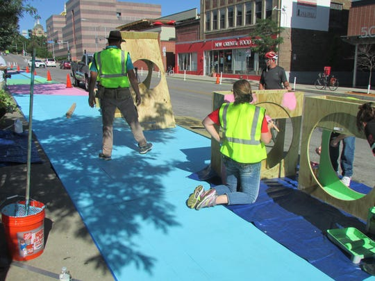 Volunteers work to temporarily transform East Grand Avenue in the East Village between Fifth and Sixth Streets as part of the Build a Better Block project.