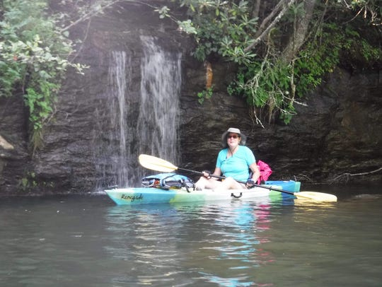 Wendy Womble relaxes in her kayak in front of a waterfall