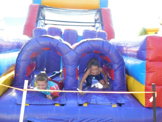 Dee Myles, 11, and John Myles Jr., 12, race through an inflatable obstacle course at Project Big Love on Saturday, July 28, 2018, at Mont Alto carnival grounds.