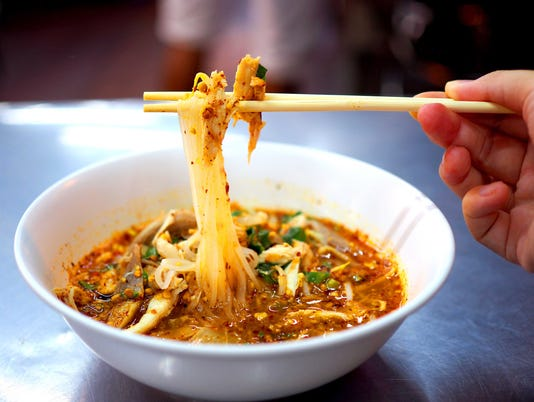 Thai local spicy chicken white noodle soup, gripping up with wooden chopsticks, right hand