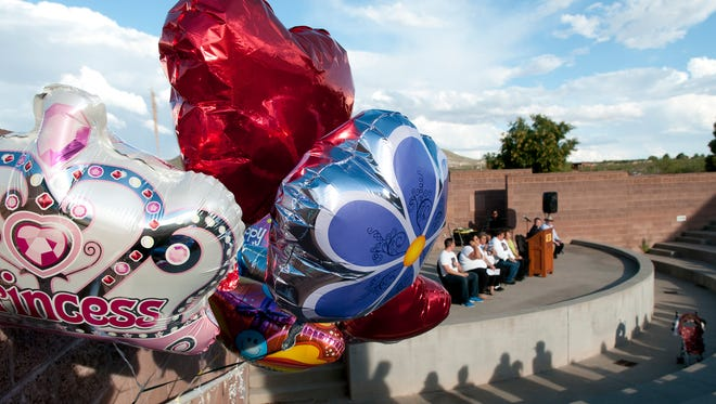 Balloons line the railing of the New Mexico Heritage Farm & Ranch Museum amphitheater as a memorial service was held in Victoria Martens' honor Sunday, Aug. 28, 2016.