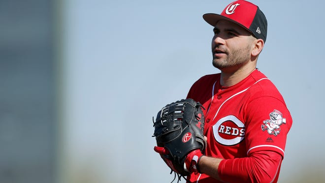 Cincinnati Reds first baseman Joey Votto (19) talks with hitting coach Don Long between reps of ground ball drills during practice at the Cincinnati Reds training complex in Goodyear, Ariz., on Wednesday, Feb. 21, 2018.