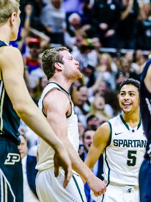 MSU's Matt Costello howls after dunking the ball over Purdue's Isaac Haas, left, during the second half of MSU's win over Purdue.