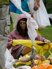 Emily Moore, 14, of Wilmington, helps out with tying bags together as part of an attempt to set a world record for plastic bag ball at the Wilmington Riverfront Saturday.