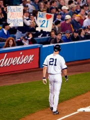 With fans showing their appreciation, New York Yankees baserunner Paul O'Neill stays close to third base after advancing on a Tino Martinez single in the first inning of World Series Game 5 against the Arizona Diamondbacks at Yankee Stadium on Thursday, Nov. 1, 2001. O'Neill, who retired after the World Series, was playing his last game in Yankee Stadium.
