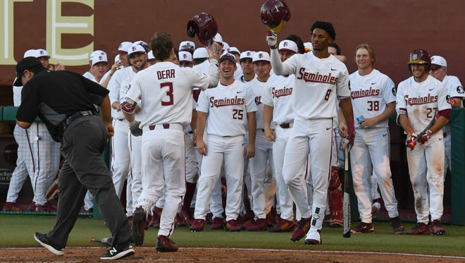 FSU sophmore infielder Nick Derr (3) celebrating with his teammates after a home run.