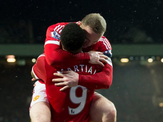 Manchester United's Wayne Rooney, top, celebrates with teammate Anthony Martial after scoring during the English Premier League soccer match between Manchester United and Swansea City at Old Trafford Stadium, Manchester, England, Saturday, Jan. 2, 2016. (AP Photo/Jon Super)