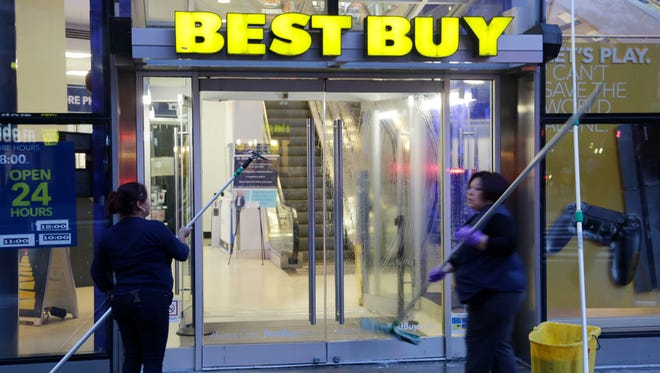 Window washers clean the entrance to a Best Buy store, Wednesday, Oct. 29, 2014 in New York. The consumer electronics retailer is based in Richfield, Minn.