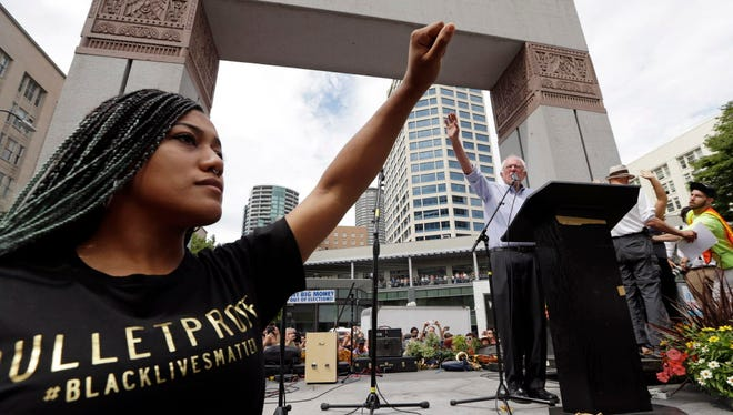 Mara Jacqueline Willaford, left, holds her fist overhead as Democratic presidential candidate Sen. Bernie Sanders, I-Vt., waves to greet the crowd before speaking at a rally Saturday, Aug. 8, 2015, in downtown Seattle. Willaford and another co-founder of the Seattle chapter of Black Lives Matter took over the microphone just after Sanders began to speak and refused to relinquish it. Sanders eventually left the stage without speaking further and instead waded into the crowd to greet supporters.