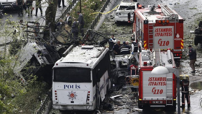 Police officers inspect the area after a bomb attack to a police bus in Istanbul, Turkey on June 7.