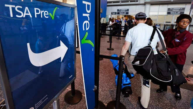 A passenger passes by a sign for the Transportation Security Administration's TSA Precheck line on June 27, 2016, in Terminal A at Logan Airport in Boston.