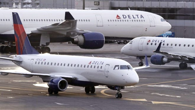 A Delta Connection Embraer 175 aircraft, foreground, taxis to a gate at Logan International Airport in Boston on Jan. 8, 2018.