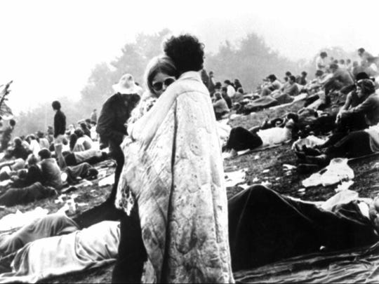 A couple embrace on a muddy hillside during the Woodstock