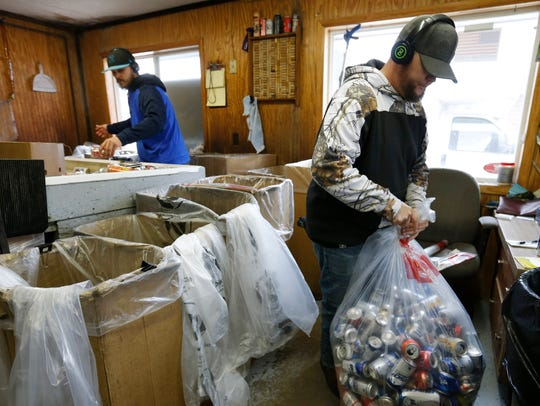 Josh Thompson, right, ties up a full bag of cans as