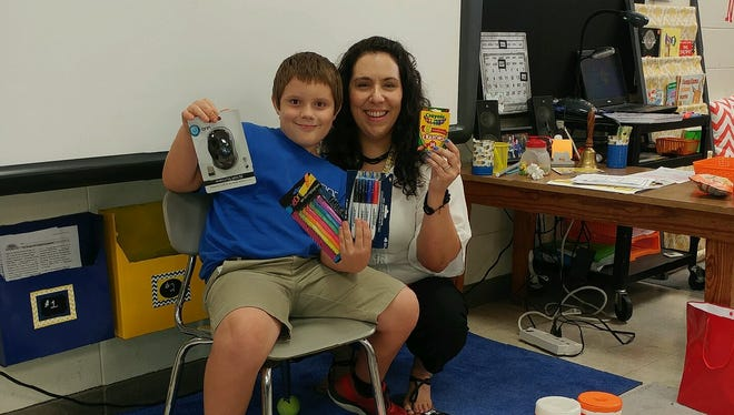 Michael Laurent, 9, delivers school supplies to Amy Muller at Duson Elementary. Laurent asked friends and family to buy supplies for Muller's class instead of birthday presents for him.