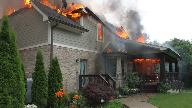 Flames engulf a house in the 6400 block of South Arlington Avenue on Indianapolis' Southside on Thursday, June 25, 2015.