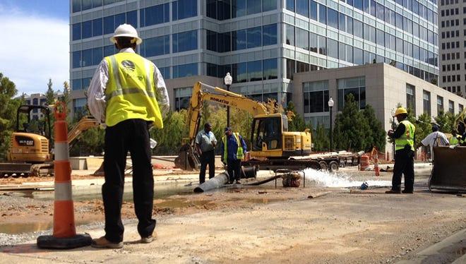 Workers repair a water line break on Capitol Street in downtown Jackson, Miss.