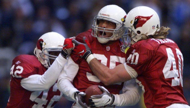 Aeneas Williams gets a hug from Pat Tillman (right) and Kwamie Lassiter after a the Cardinals defeated the Cowboys on Jan. 2, 1999, in the NFL playoffs.