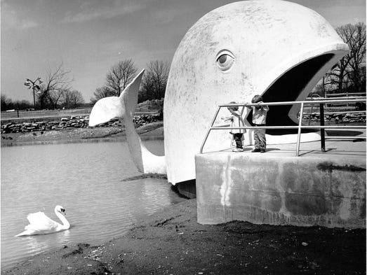 Two young children, oblivious to the enormous Willie The Whale over their shoulders, try to attract a swan in the pond at the Indianapolis Zoo's original E. 30th Street location a week before the zoo opened for its second season in 1965.