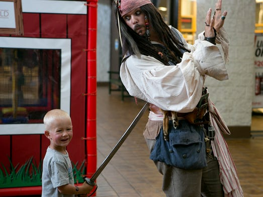 Dakota Kraft of Edgar, 3, poses for a photo with Minnesota's Jack Sparrow during the Kids Expo at Marshfield Mall, Saturday, Aug. 16, 2014. This year's pirate themed Kids Expo featured Joshua Godfredson who performs as Minnesota's Jack Sparrow.