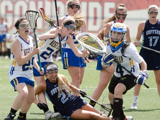 Suffern's Co-Captain Caitlin Leary gets knocked down  during the first half against West Islip in the Class A semi-final lacrosse match at SUNY Cortland, June 6, 2014.