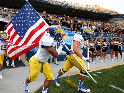 Delaware's Derrick Saulsberry (left) and Justin Glenn lead the team onto the field before taking on Pittsburgh, Saturday, August 30, 2014 at Heinz Field in Pittsburgh, Pa.