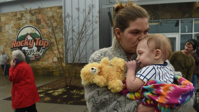 Shari Deason holds 14 month-old son William outside of the Rocky Top Sports Center, serving as a Red Cross shelter, next door to the TEMA command center at Gatlinburg-Pittman High School in Gatlinburg, Tenn. Tuesday, Nov. 29, 2016. More than 2000 people have checked in to various shelters. Deason said she had to leave all of her belongings behind when evacuated from a hotel overnight.
