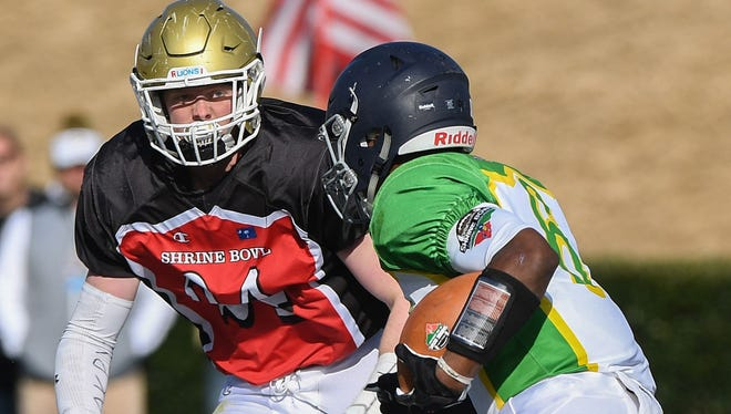 South Carolina linebacker Jake Venables, left, of Daniel sizes up North Carolina running back Ricky Person during the Tar Heels' 55-24 win in Saturday's Shrine Bowl at Gibbs Stadium in Spartanburg.