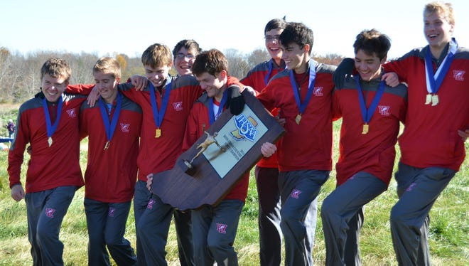 Andrius Kriauchinunas (from left), Dylan Williams, Evan Johnson, Jake Cohen, Travis Shinsky, Dom Paticsil, Cooper Williams, Logan Berndt of the West Lafayette boys cross country team do a celebratory dance with the state championship trophy.