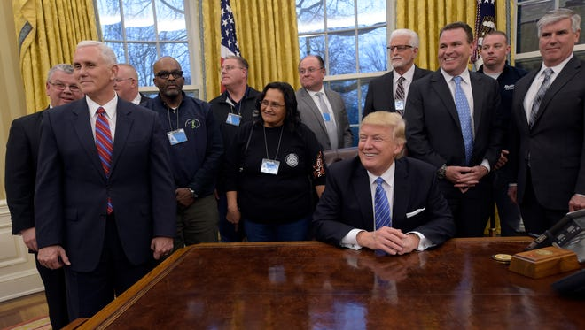 President Donald Trump poses with union leaders in the Oval Office of the White House on Monday, Jan. 23, 2017, in Washington. Vice President Mike Pence is at left.