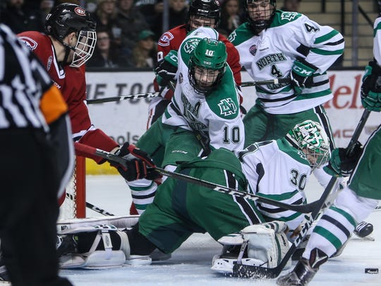 UND goalie Matt Hrynkiw (30) and Johnny Simonson (10)