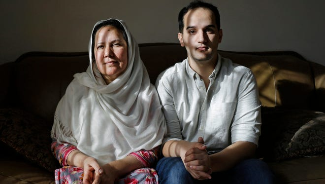 Shamim Syed, left, whose son Adnan was convicted for the 1999 murder of his ex-girlfriend and whose case is being revived in a wildly popular podcast, poses for a photograph alongside her son Yusef in her home, Wednesday, Dec. 10, 2014, in Baltimore. A Maryland appeals court recently showed interest in the case and will hold a hearing in January weighing arguments that the man had ineffective counsel. (AP Photo/Patrick Semansky)