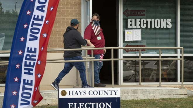 Election clerk Wes Garcia, right, holds the door for a voter Monday at an early voting location at the Hays County Elections Office in San Marcos. A federal judge late Tuesday ordered that masks be worn in polling places.