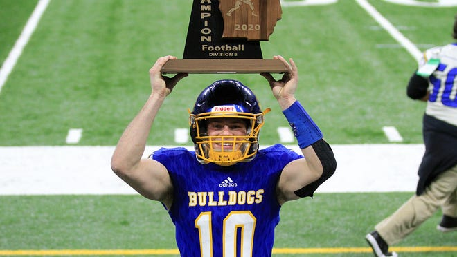 Sam Todd hoists the state championship trophy following the Bulldog win on Friday.