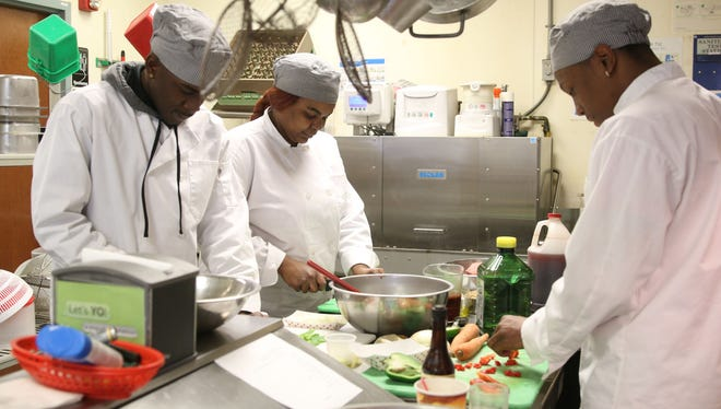 James Ricks of Asbury Park, Zykia Reevey of Long Branch, and Myshon McKinnon of Asbury Park prepare a meal. Food Bank of Monmouth and Ocean Counties Chef Ray Cattley instructs students during a 13 week culinary arts program. The course aims to prepare people for jobs in the food service industry. In May the program will be offered at the new BEAT center in Toms River which includes the second permanent Jon Bon Jovi Soul Kitchen. Neptune, NJ Wednesday, March 2, 2016@DhoodHood