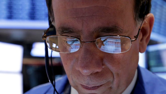 The handheld device of trader Sal Suarino is reflected in his glasses as he works on the floor of the New York Stock Exchange.