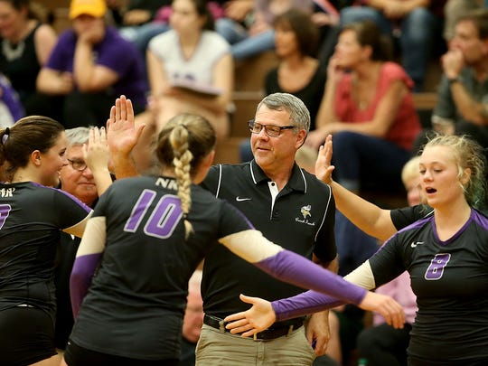 North Kitsap volleyball coach Tim French high fives his team during a timeout against South Kitsap in Port Orchard on Thursday, September 7, 2017.