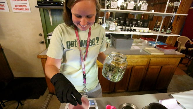 Robynlee Sutter, a budtender at CannaMedicine Marijuana Dispensary, weighs marijuana before selling it to a customer on Thursday, Sept. 24, 2015, Salem, Ore.