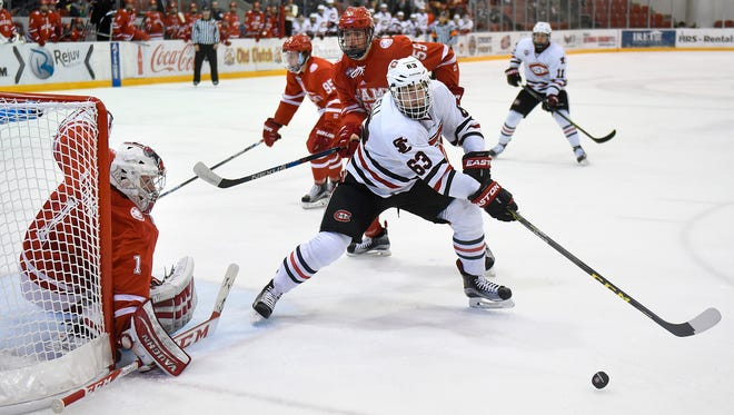 St. Cloud State's Patrick Russell tries to get control of the puck in front of Miami goaltender Jay Williams during Saturday's game at the Herb Brooks National Hockey Center in St. Cloud.