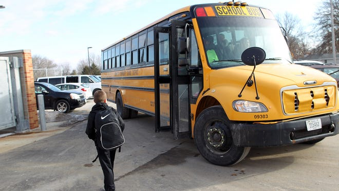 A Penn Elementary student gets on a bus after school in North Liberty on Thursday, Feb. 4, 2016.